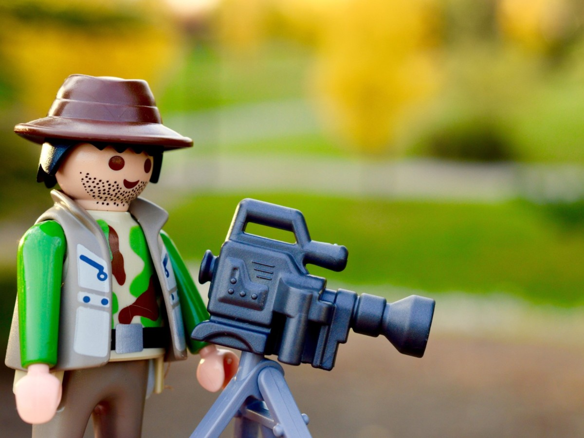 A Lego character recording a video wearing outdoor clothing